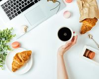 La surface de la table blanche de bureau avec l'ordinateur portable, croissant, macarons photos libres de droits