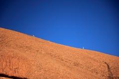 La surface en pierre rougeâtre de la roche d'Ayers avec deux IR s'élevant image stock