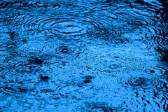 La surface modifiée la tonalité bleue de l'eau ondule et éclabousse sous la pluie de chute Photos stock