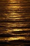 La surface ondulée d'océan rougeoie avec la couleur de cuivre riche au crépuscule photographie stock