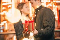 La surprise romantique pour Noël, femme reçoit un cadeau de son ami Photos stock