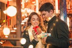 La surprise romantique pour Noël, femme reçoit un cadeau de son ami Image libre de droits