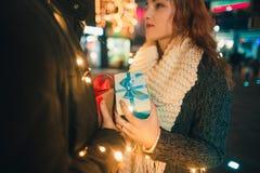 La surprise romantique pour Noël, femme reçoit un cadeau de son ami Images stock