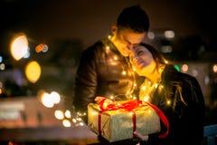 La surprise romantique pour Noël, femme reçoit un cadeau de son ami Photographie stock libre de droits