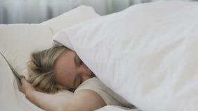 La sveglia che sveglia lo studente, copertura della ragazza con la coperta e continua dormire video d archivio
