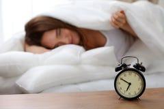 La sveglia che sta sul comodino già ha suonato il primo mattino per svegliare la donna a letto che dorme nel fondo Immagini Stock