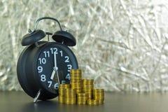 La sveglia e conia le pile sulla tavola di funzionamento, tempo per il risparmio Fotografia Stock Libera da Diritti