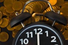 La sveglia e conia le pile sulla tavola di funzionamento, tempo per il risparmio Fotografie Stock Libere da Diritti