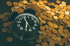 La sveglia e conia le pile sulla tavola di funzionamento, tempo per il risparmio Fotografie Stock