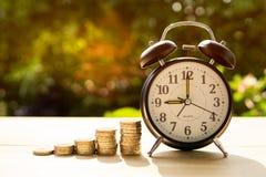 La sveglia e le monete con luce solare nel parco rappresenta l'inizio dei soldi di risparmio fotografia stock