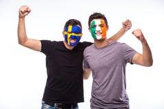 La Svezia contro l'Repubblica Irlandese su fondo bianco I tifosi delle squadre nazionali celebrano, ballano e gridano Fotografia Stock