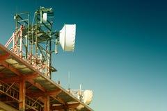 La télécommunication domine avec plusieurs antennes et ciel bleu d'espace libre sur le fond Image filtrée : effet de vintage trai Photographie stock