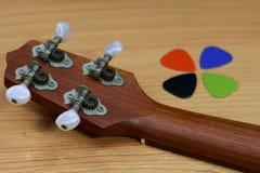La tête de l'ukulélé et la guitare colorée sélectionnent sur le fond en bois photos libres de droits
