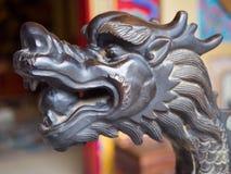 La tête en bois découpée d'un dragon noir Photo stock