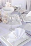 La Tabella è servito con i piatti ed i bicchieri di vino del quadrato bianco Fotografia Stock