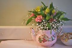 La Tabella con la ciotola antiquata di zucchero e della teiera ha riempito di fiori freschi fotografia stock