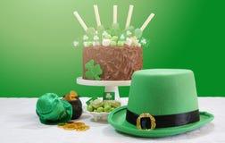 La Tabella del partito del giorno del ` s di St Patrick con il dolce di cioccolato, il cappello del leprechaun e la lente si svas Fotografia Stock Libera da Diritti