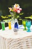 La tabla con el ramo de rosas con los vidrios acerca a la charca Fotos de archivo libres de regalías