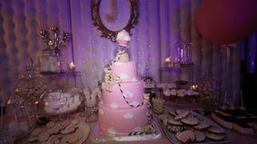 La tabla con los dulces, torta rosada 1 año, barra de caramelo, los dulces deliciosos en el caramelo golpea, torta con un cachorr almacen de metraje de vídeo