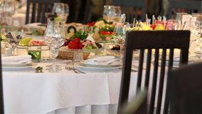 La tabla de banquete con la decoración, el camarero abre una botella de vino, un banquete en un restaurante, interior del restaur metrajes