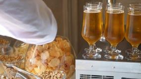 La tabla de banquete con los productos de carne, pistachos, aceitunas, secó los pescados, microprocesadores y otros bocados, en r almacen de video