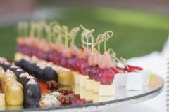 La tabla de banquete del abastecimiento con los bocados de la comida, los bocadillos, las tortas, las tazas y las placas cocidos, Imagen de archivo libre de regalías