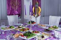 La tabla de cena elegante Tabla de la boda adornada con las velas, servida con los cubiertos y loza y cubierta con un mantel P Foto de archivo