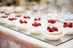 La tabla de comida fría adornada es tortas y bocados imagenes de archivo