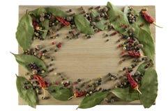 La tabla de cortar de la cocina, dispersó las especias bajo la forma de marco imagenes de archivo