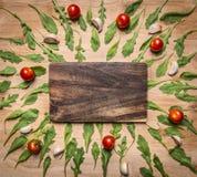 La tabla de cortar con los tomates y las hierbas alrededor del lugar para el texto, enmarca la opinión superior del fondo rústico Foto de archivo libre de regalías
