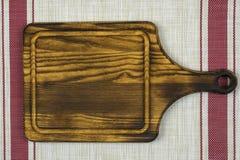 La tabla de cortar miente en un fondo blanco con dos rayas rojas fotografía de archivo