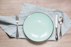 La tabla de la elegancia fijó con la placa y las servilletas de la turquesa en tablero de madera montante rústico Imagen con el e fotos de archivo