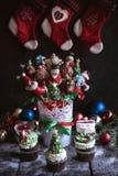 La tabla de la Navidad con las tortas y la torta de la taza hace estallar Fotos de archivo libres de regalías