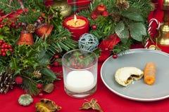 La tabla de la Navidad con un vidrio de leche y pica la empanada Imagenes de archivo