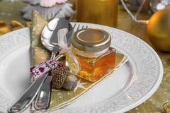 La tabla de la Navidad fijó con el regalo del tarro de la miel para las huéspedes Foto de archivo libre de regalías