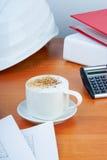 La tabla de la oficina con la taza de café, trabaja las herramientas esenciales y el casco blanco fotografía de archivo libre de regalías