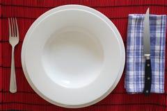 La tabla de los cubiertos y de la loza fijó con el plato vacío blanco foto de archivo