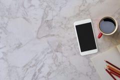 La tabla de mármol del escritorio con una taza roja y el color dibujan a lápiz Imágenes de archivo libres de regalías