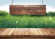 La tabla de madera con el colgante de la muestra de madera en la naturaleza verde empañó el fondo Imagen de archivo