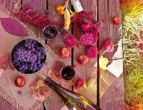 La tabla de madera con el vino y las uvas en otoño cultivan un huerto Foto de archivo libre de regalías