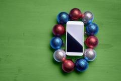 La tabla de madera con un teléfono y las decoraciones de la Navidad Foto de archivo