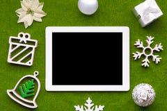 La tabla de madera con una tableta y las decoraciones de la Navidad Concepto de la maqueta de la Navidad Fotos de archivo libres de regalías