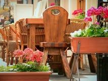 La tabla de madera del café del verano al aire libre en el phono florece Imagen de archivo