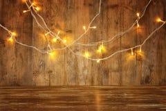 La tabla de madera del tablero delante de la guirnalda caliente del oro de la Navidad se enciende en fondo rústico de madera capa Imagen de archivo libre de regalías