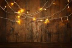 La tabla de madera del tablero delante de la guirnalda caliente del oro de la Navidad se enciende en fondo rústico de madera capa Foto de archivo