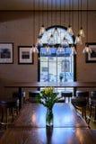La tabla de madera oscura con las flores de corte y el colgante frescos de edison se enciende fotos de archivo