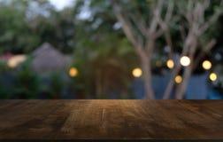 La tabla de madera oscura vacía delante del extracto empañó el fondo del bokeh del restaurante Puede ser utilizado para la exhibi imagen de archivo