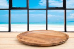 La tabla de madera de la perspectiva y la bandeja de madera en el top sobre fondo de la opinión del mar de la falta de definición fotos de archivo libres de regalías