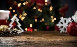 La tabla de la Navidad borrosa enciende el fondo, escritorio de madera en el foco, tablón de madera de Navidad, empaña el sitio c foto de archivo libre de regalías