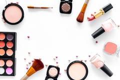 La tabla de trabajo de Visagiste con los cosméticos decorativos de tonos beige y desnudos fijó la maqueta blanca de la opinión su fotos de archivo libres de regalías